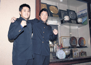 歴代野球部のトロフィーなどの前で健闘を誓い合う滝川西の堀田(左)と鈴木
