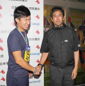 16年、桐生(左)と握手を交わす伊東強化委員長