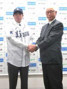 入団会見を終えた高木勇人と握手を交わす西武の鈴木球団本部長(右)