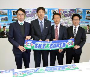 事務所開きでチームフラッグを持ち、意欲を見せる藤川代表(左から2人目)らクラブ役員
