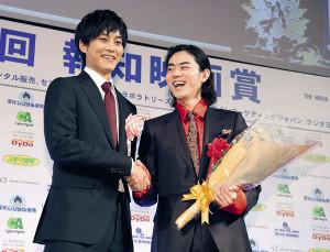 松坂桃李(左)に花束を手渡され、笑顔で握手をする主演男優賞の菅田将暉(カメラ・矢口 亨)