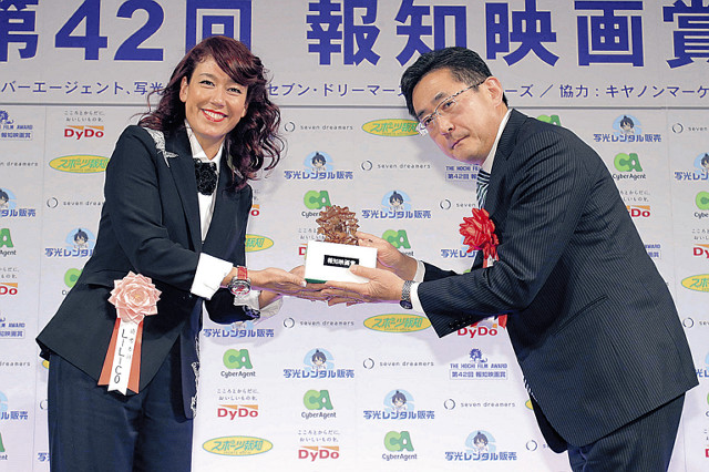 アニメ作品賞を受賞した東宝東和・星野智彦社長にブロンズ像を贈るLiLiCo