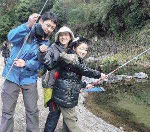 ニジマスを釣り上げて喜ぶ岡さん家族