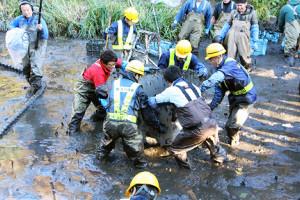 大きな鉄管を使い、懸命に池のヘドロを除去する田村淳(左)と作業員ら