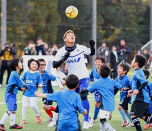 サッカー教室に参加し、子供たちと競り合う本田(中央=カメラ・川口 浩)