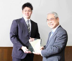 札幌学生野球連盟の西村会長(右)から盾を授与された北海道教育大岩見沢の斉藤