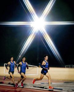 ナイター照明の下、2000メートルインターバル走をする法大・青木(右)ら(カメラ・佐々木 清勝)