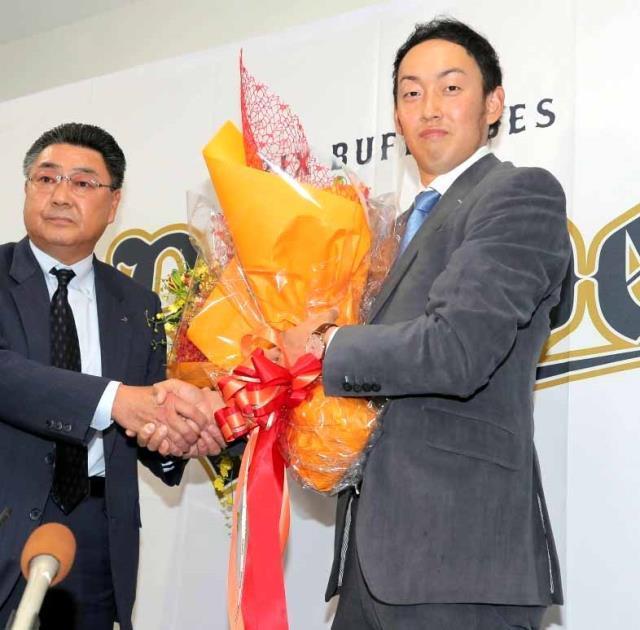 会見後、長村球団本部長から花束を受け取る平野(右)