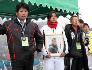 試合中、女子マネジャーの持つ浜口前監督の遺影とともに試合を見守る和歌山工・岡本監督(左)
