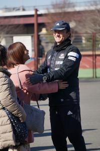 サポーターの女性から激励を受け、笑顔で応えるエリク・モンバエルツ監督