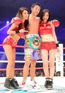 7回TKO勝利で初防衛に成功した清水聡は、ラウンドガールを抱き寄せ笑顔を見せた