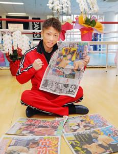 WBOスーパーフライ級で防衛戦を制した井上尚弥は勝利を伝えるスポーツ報知を手に笑みを浮かべた