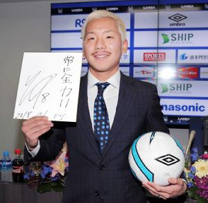 リーズへの移籍会見を終えて、目標を記した色紙を手に笑顔をみせる井手口(カメラ・石田 順平)