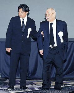 息子の克則氏(左)に支えられる克也氏
