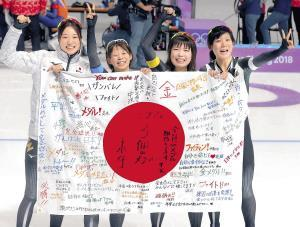 女子団体追い抜きで優勝した(左から)菊池彩、高木菜、佐藤、高木美は応援メッセージが書かれた日の丸を手に喜ぶ(カメラ・酒井 悠一)