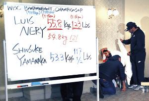 計量をパスできず、結果が書かれたホワイトボードの奥で肩を落とすネリ(右奥)