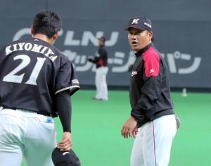 試合前、清宮(左)から挨拶を受ける井口監督