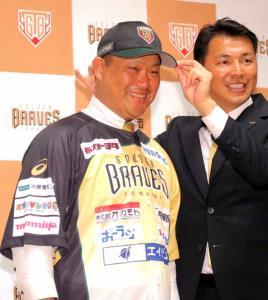 栃木ゴールデンブレーブスの帽子をかぶり笑顔を見せる村田(右は辻監督)