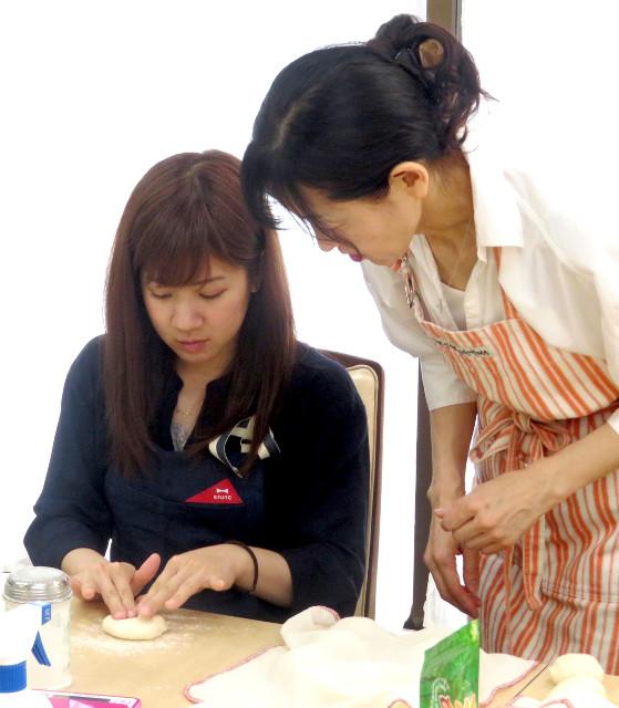 伊藤さん(右)の指導を受けながら、生地の形を整える