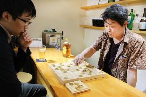 「あるじゃん」の店長・福田雄一さん。来客が多い時はカウンター越しに三面指しをすることもあるという(カメラ・甲斐 毅彦)