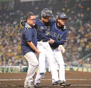 8回2死二塁、勝ち越しの右越え適時三塁打で足を痛めた吉田正(中央)は抱えられベンチに戻る