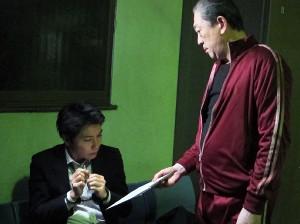 映画「審判」での坂東彌十郎(右)。えんじ色のジャージー姿が強烈だ。左は主演にわつとむ