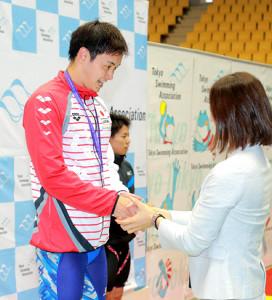 プレゼンターの寺川綾さん(右)と笑顔で握手する金子雅紀