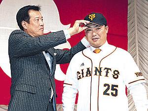FA権行使で巨人への入団会見を終え、原辰徳監督(左)から帽子をかぶせてもらう村田修一