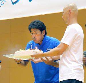 46歳の誕生日にサプライズで贈られたケーキのろうそくを吹き消す侍ジャパン・稲葉監督(右は野球解説者の森本稀哲氏)