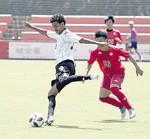 北翔大との練習試合でボールキープする、札幌の練習生MFマルコス・ヴィニシウス(左)