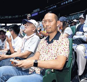 甲子園のスタンドで観戦する、なきぼくろ氏(右)