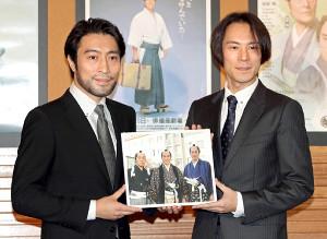 思い出の写真を手にする長男・夏原涼(右)と次男・加藤頼
