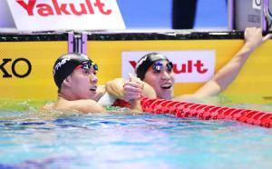 男子200メートル平泳ぎで優勝した渡辺一平(左)は、レース後に小関也朱篤と握手を交わす(カメラ・酒井 悠一)