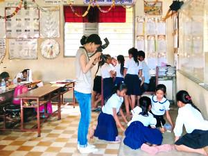 カンボジアを取材に訪れた際の一コマ。ファインダー越しにに子供たちの笑顔を写す(古賀さん提供)
