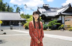 本堂の前でたたずむ写真家・古賀絵里子さん