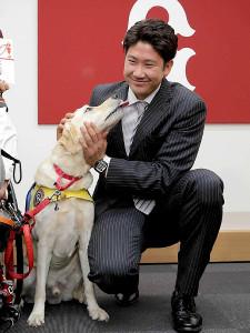 介助犬育成普及のために支援金を贈呈し、介助犬のクウとふれあう菅野