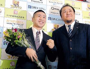 現役引退会見で花束を手に笑顔を見せる山中竜也(右は山下会長)