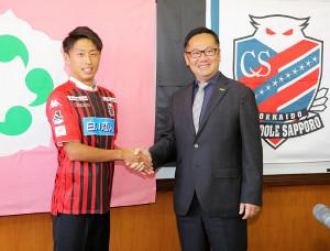 札幌のユニホームに袖を通し、笑顔で握手を交わす青森山田・檀崎(左)と札幌・竹林チーム強化部長