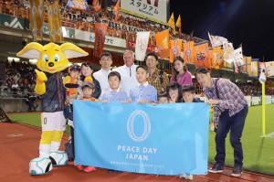 試合前、招待した子どもたちと記念撮影したヨンソン監督(後列中央)