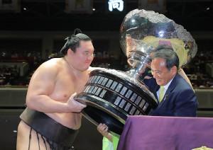 菅官房長官から総理大臣賞を贈られる白鵬(左)(カメラ・能登谷 博明)