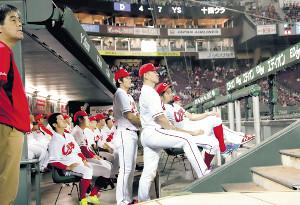 試合後、大型スクリーンで放映された中日・ヤクルト戦を見つめる広島ナイン。ベンチで待機もむなしく、優勝は持ち越しとなった(カメラ・馬場 秀則)