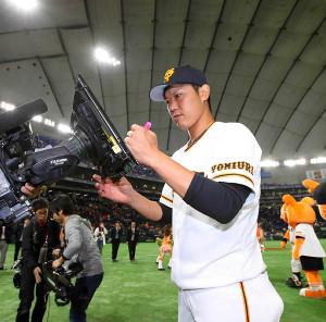 東京ドームでのヒーローインタビューを終え、カメラのレンズの前に設置された透明のアクリル板に左手でサインする内海