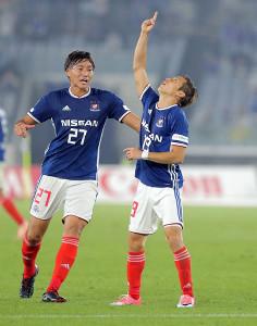 前半、同点ゴールを決めた横浜Mの仲川は天を指さす(右)