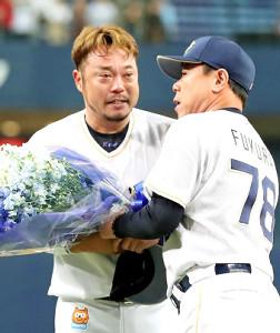 5日の引退セレモニーで福良監督(右)から花束を受け取る小谷野