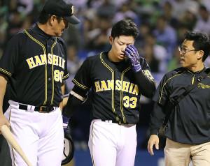 3回1死一、三塁、自打球を左目に当て交代する糸原(左は片岡コーチ)