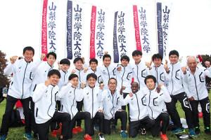 山梨学院大は上田監督(前列左から4人目)を中心に笑顔でガッツポーズ