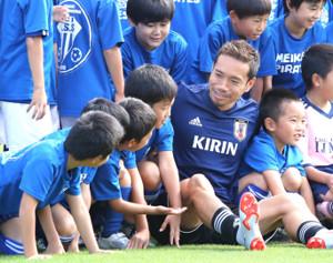 練習前の記念撮影で、少年たちと和やかに交流する長友(カメラ・竜田 卓)