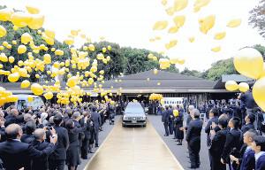 大相撲の通算白星数である673個の風船が舞うなか、輪島さんの棺を載せた車は黄金のカーペットの上を進んだ(カメラ・酒井 悠一)