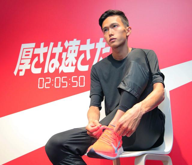 自ら更新した男子マラソンの日本記録のボードをバックにインタビューに応えた大迫(カメラ・酒井 悠一)