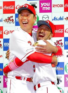 18日の巨人戦で勝利した後、お立ち台で満面の笑みで抱き合う新井(左)と菊池